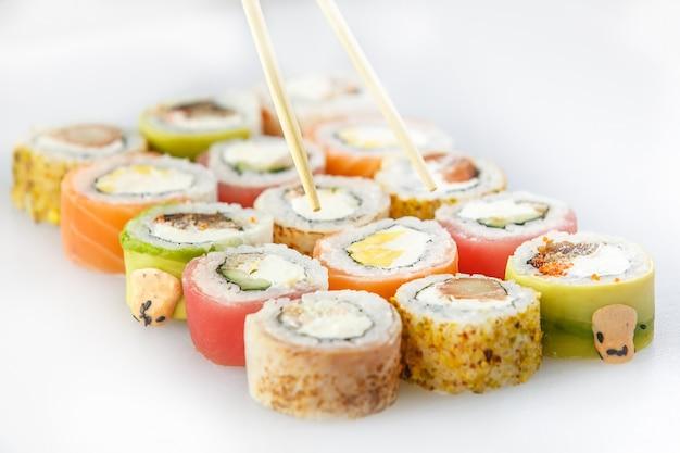 Суши-сет. роллы с лососем и овощами, вегетарианские, на деревянной тарелке, изолированные на белой поверхности