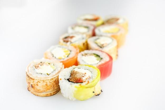 초밥 세트. 흰색 표면에 고립 된 나무 접시에 연어와 야채, 채식 롤