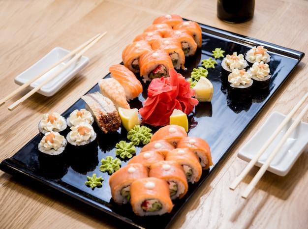 寿司セット。木の板にサーモン、ウナギ、赤キャビアを巻き。飲食店。