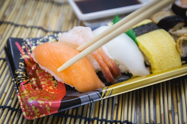 Sushi set sashimi and rolls served on traditional plate and mat