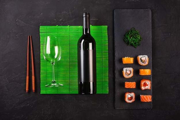 Sushi set sashimi and sushi rolls, bottle of wine and a glass served on stone slate
