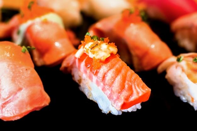 Sushi set sashimi and sushi rolls served on black stone slate with white background