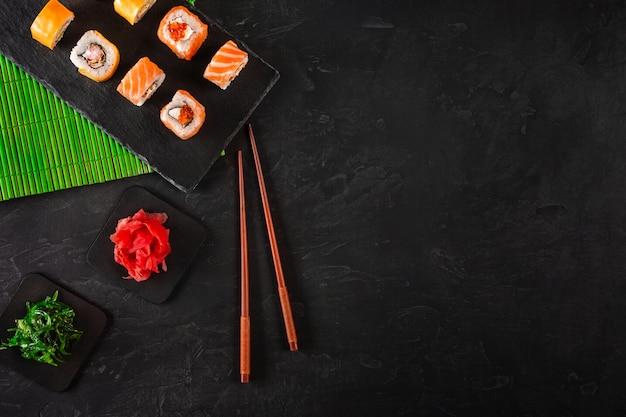 Sushi set sashimi and sushi rolls served on stone slate