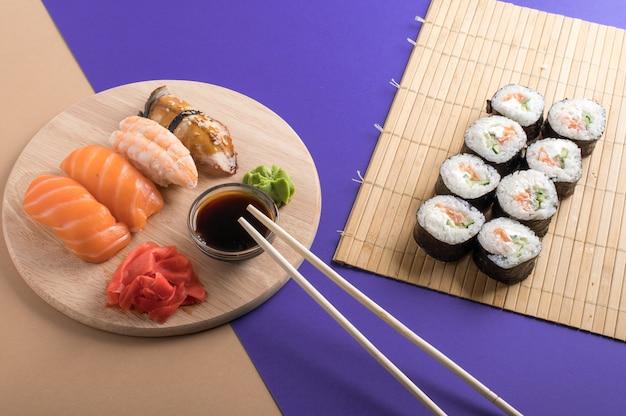 サーモン、エビ、うなぎ、巻き寿司の刺身。新鮮な寿司と木の板で提供されるロールのクローズアップ。