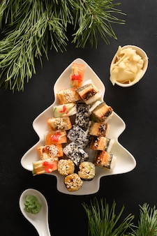 Sushi set served in plate as christmas tree with festive decoration on black background. view from above.