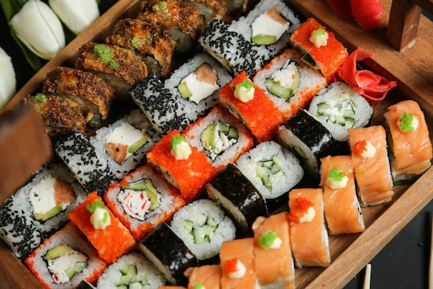 Sushi set with avocado, salmon, crab, sesame seeds, ginger and wasabi