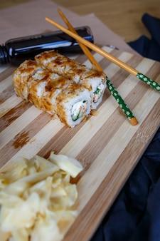 ウナギ、サーモン、マグロ、エビ、イクラ、トビコのフライングフィッシュローから作られたさまざまな種類のロールと刺身がセットされた寿司。黒いコンクリートのキッチンテーブルでの汎アジア料理とアジア料理。