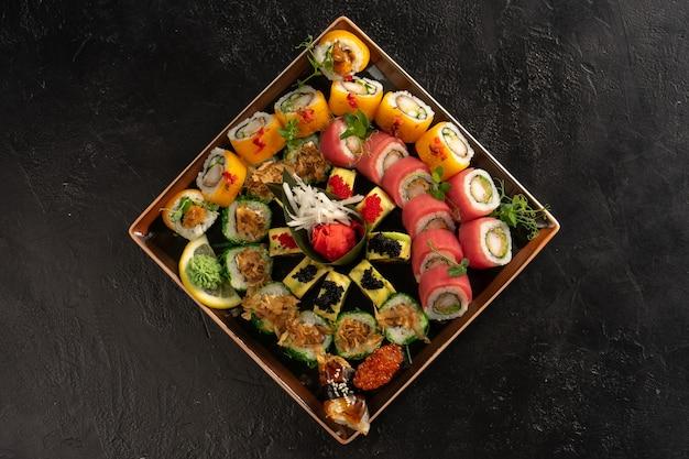 ウナギ、サーモン、マグロ、エビ、イクラ、トビコのフライングフィッシュローから作られたさまざまな種類のロールと刺身がセットされた寿司。