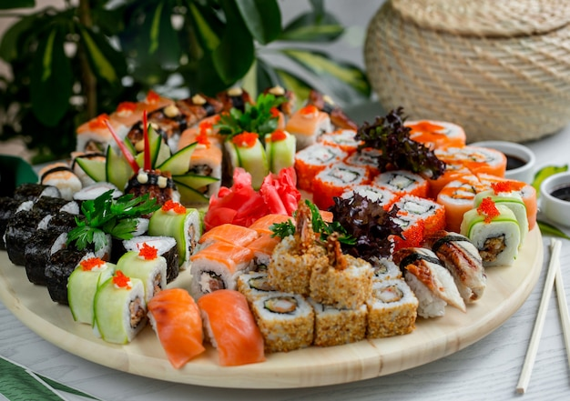 Sushi set with hot and cold rolls on wood platter