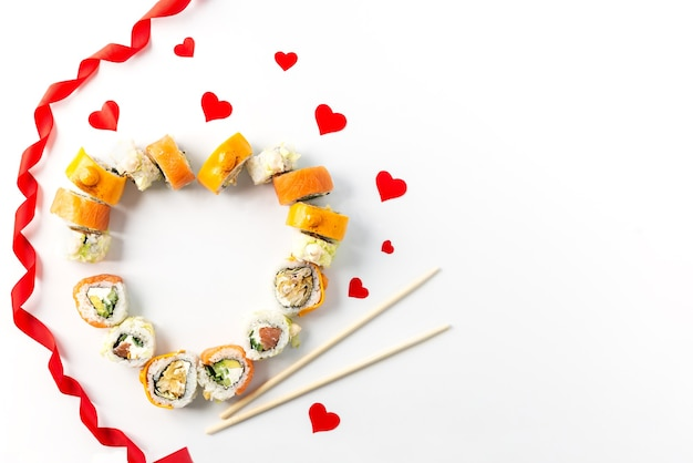 Sushi set with red hearts and ribbon on a white plate, valentine's day.