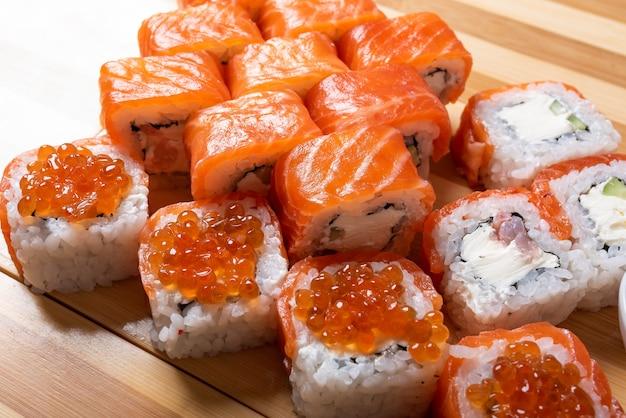 Суши-сет с лососем филадельфия с икрой с имбирем и васаби крупным планом