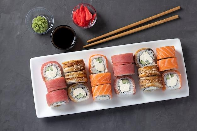 灰色の背景の白いプレートにサーモン、マグロ、スモークウナギとフィラデルフィアチーズをセットした寿司。醤油、わさび、生姜の酢漬け、お寿司のスティックを添えて。上から見る