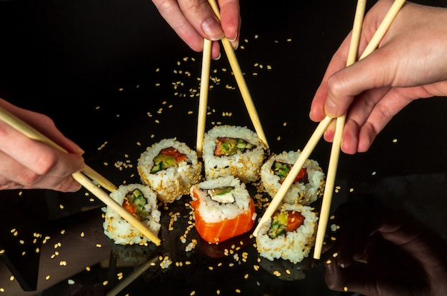 Sushi set with sesame seeds on a black table in a restaurant. women is hands hold sushi rolls with sticks