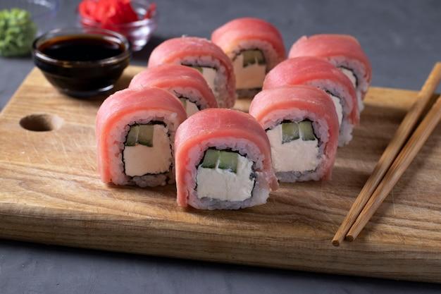 Суши с тунцом и сыром филадельфия на деревянной доске на сером фоне. здоровая пища. крупным планом