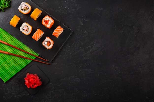 Sushi set with wasabi and ginger on black stone tray on black table.
