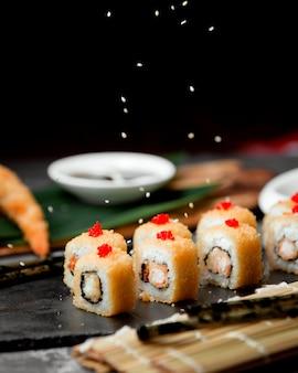 Суши с желтой икрой на столе