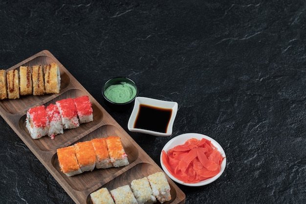 Sushi set on a wooden board with wasabi, ginger and soy sauce.