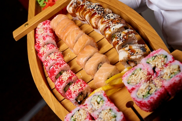 Sushi set on a wooden boat in the hands of the cook.