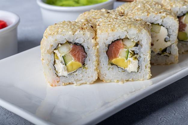 寿司は白い皿にニギリ、裏巻き、カリフォルニア、フィラデルフィアをセットします。近くの生姜とわさび。