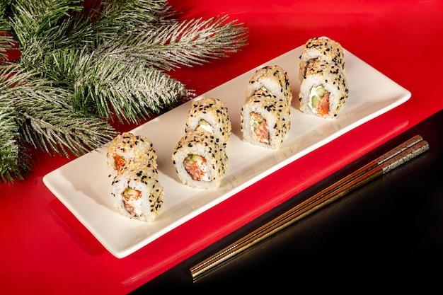 Суши-наборы нигири, урамаки, калифорния, филадельфия, на белой тарелке. на красном фоне. скопируйте пространство.