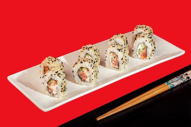 Sushi sets nigiri, uramaki, california, philadelphia, on a white plate. on a red colored background. copy space.