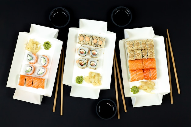 Sushi sets in paper take away containers with chopsticks and soy sauces top view