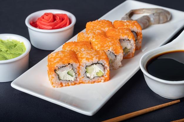寿司は白い皿にカリフォルニア州裏巻き、フィラデルフィアを設定します。近くの生姜とわさび。