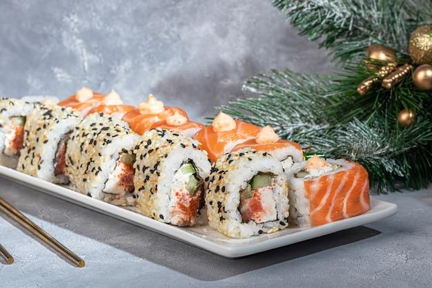 Суши-наборы урамаки, калифорния, филадельфия, на белой тарелке. новый год и праздничная концепция. на светло-сером фоне. скопируйте пространство.