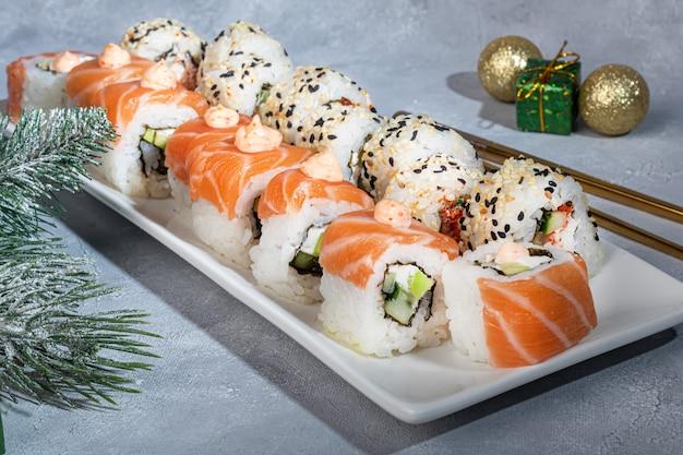寿司は白い皿にカリフォルニア州裏巻き、フィラデルフィアを設定します。新年とお祭りのコンセプト。明るい灰色の背景。スペースをコピーします。
