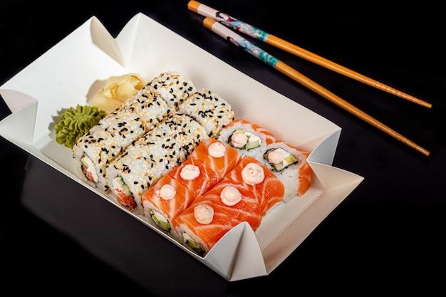 Sushi sets uramaki, california, philadelphia, on a white plate. festive, new year concept. against a dark reflective background. copy space