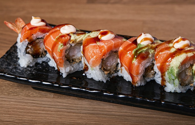 Sushi stuffed with prawn covered with salmon and avocado.