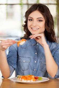 寿司の時間。寿司を食べて、レストランに座って笑っている美しい若い女性