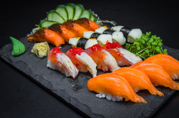 Суши, традиционная японская кухня. несколько вкусных суши на украшенной тарелке,