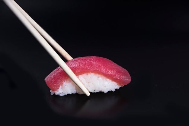 Sushi tuna nigiri in chopsticks over black