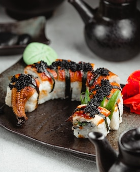 Sushi unagi rolls with black caviar on black plate.