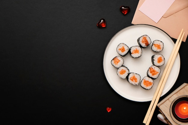 Sushi for valentines day - roll in heart shape, on plate on black background. flat lay. space for text.