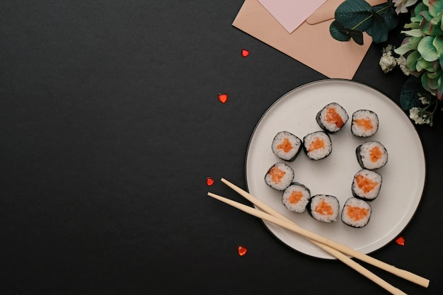 Sushi for valentines day - roll in heart shape, on plate on black background. space for text.