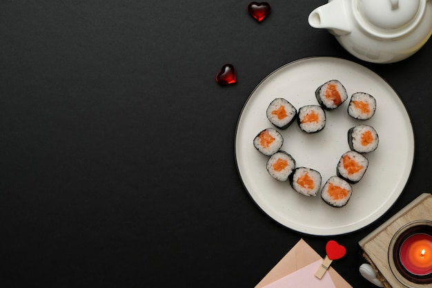 Sushi for valentines day - roll in heart shape, on plate. flat lay.