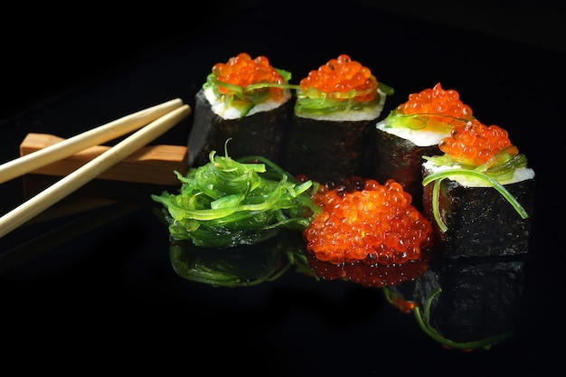 Sushi with caviar and algae salad next to chopsticks on a black with reflection.