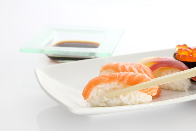 Sushi with chopsticks in white