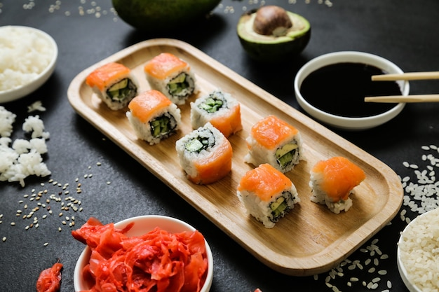 Sushi with cucumber, ginger, wasabi, soy sauce and sesame seeds