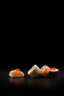 Sushi with red caviar on a black table. macro close up.