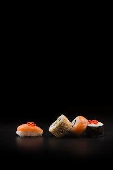 검은 테이블에 빨간 캐 비어와 초밥입니다. 매크로를 닫습니다.