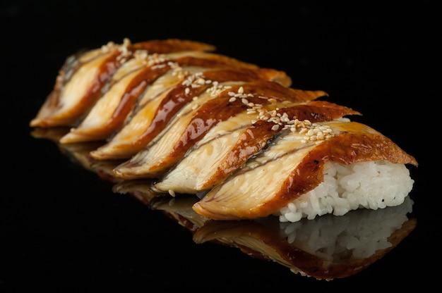 反射のある暗い背景にご飯とゴマの寿司