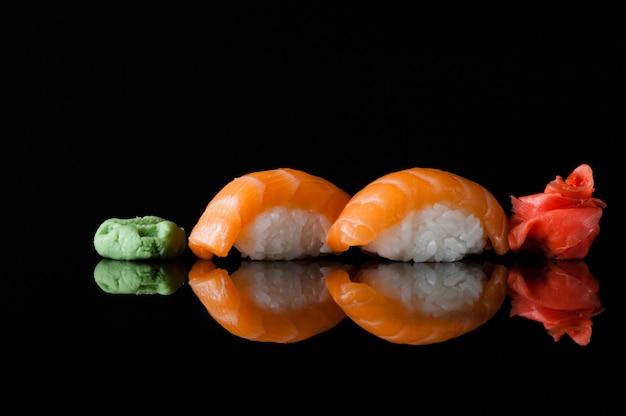 反射と黒の背景にご飯とわさびと寿司