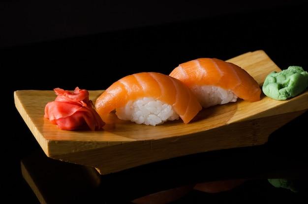 暗い背景の木の板にご飯とわさびと寿司