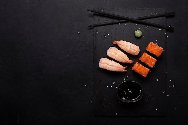 Суши с креветками и роллами на черной доске