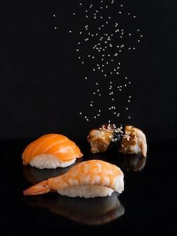 Суши с креветками, лососем и угрем на темном фоне с летающими семенами кунжута