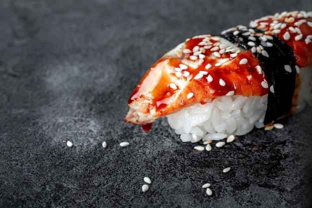 돌 배경에 훈제 장어와 참깨가 있는 초밥. 일본 요리 우나기 스시, 클로즈업