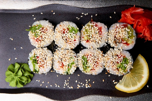 Sushi with wasabi and ginger on the plate.